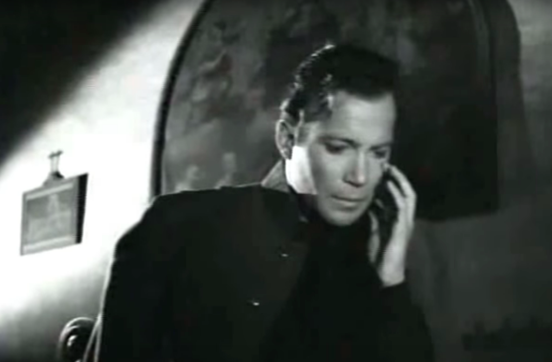Young William Shatner sits in shadowy church looking sad and confused